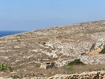 Pobřeží maltského ostrova Gozo s kamennými střílnami